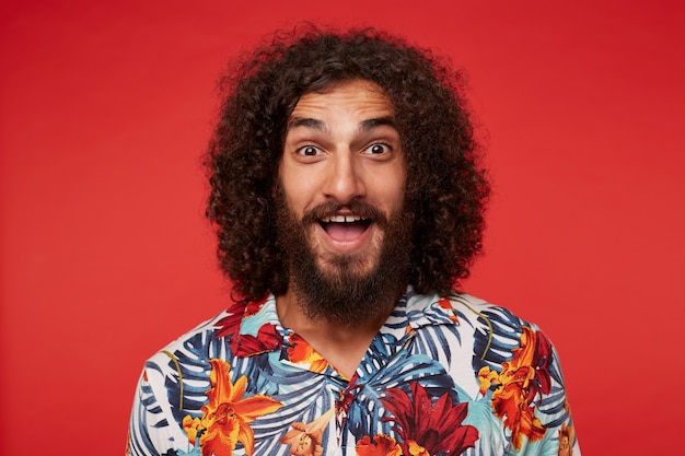 Studio photo of cheerful pretty young curly bearded male with curly brown hair standing against red background in shirt with floral print, looking happily to camera with wide mouth opened