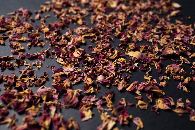 Studio photo of dried tea rose leaves, on the black table.