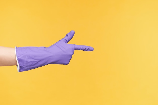 Studio photo of fair skinned hand in rubber glove being raised while pointing aside with index finger, being isolated over yellow background while cleaning house