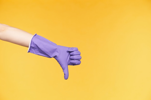 Foto di studio della mano sollevata dalla carnagione chiara rivolta verso il basso con il pollice mentre esprime emozioni negative, mostrando antipatia mentre posa su sfondo giallo