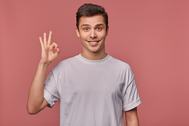 Studio photo of joyful young brown eyed man with dark hair posing over pink background in grey t-shirt, looking to camera happily and smiling widely, raising hand with ok gesture