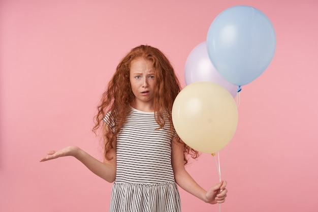 Studio photo of little girl with red curly hair wearing casual hairstyle standing over pink background, looking at camera with confused face and raising palm up, holding air balloons