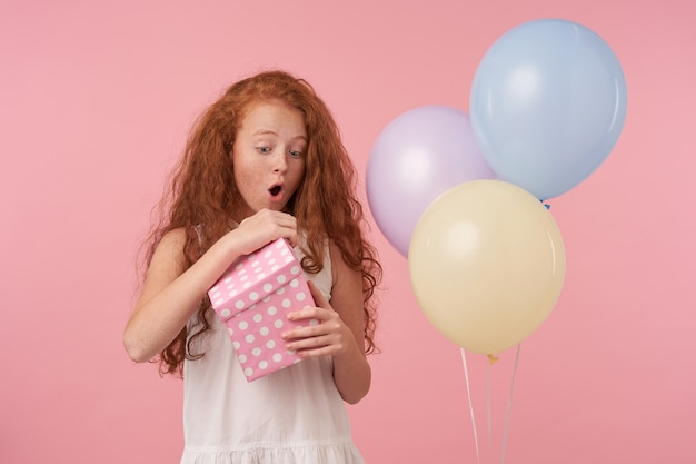 Foto di studio di ragazzino femmina bella rossa in abito elegante che celebra la festa, confezione regalo di disimballaggio con faccia eccitata, in posa su sfondo rosa con palloncini colorati