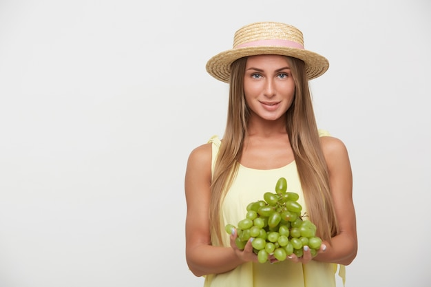Studio photo of lovely young long haired blonde lady in straw hat smiling gently while standing over white background with bunch of grapes, dressed in casual clothes