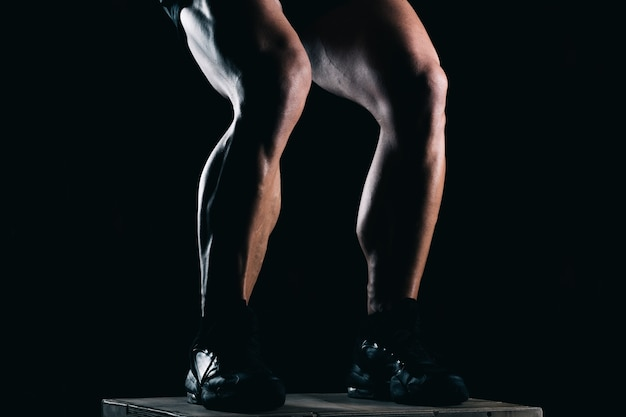 Studio photo of the lower part of a strong mans legs with black background