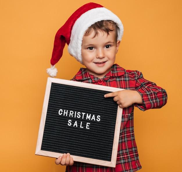 Студийное фото мальчика в рождественской пижаме и шляпе на желтом фоне с доской для писем с текстом счастливого рождества в его руках.