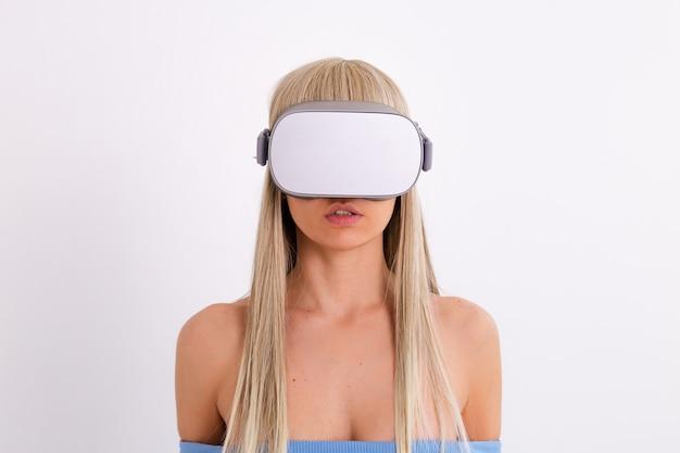白地にバーチャルリアリティメガネをかけて暖かい青のファッショナブルなスーツを着た若い魅力的な女性のスタジオ写真