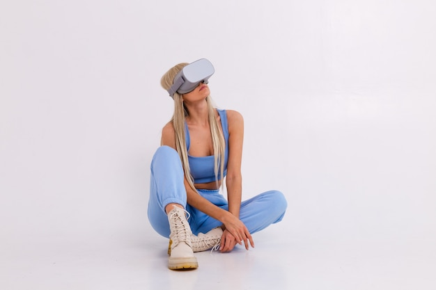 バーチャルリアリティメガネをかけて暖かい青のファッショナブルなスーツを着た若い魅力的な女性のスタジオ写真