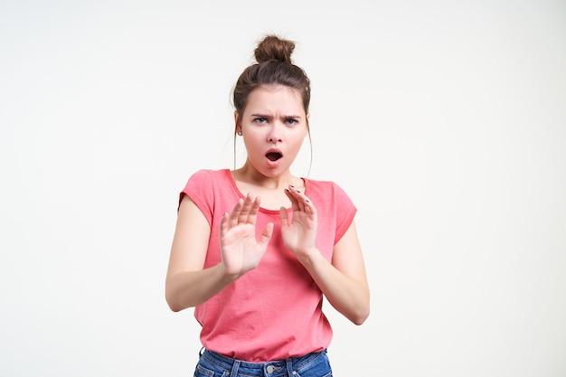Студийное фото испуганной молодой шатенки, испуганно смотрящей в камеру с открытым ртом и поднимающей руки в жесте остановки, стоя на белом фоне