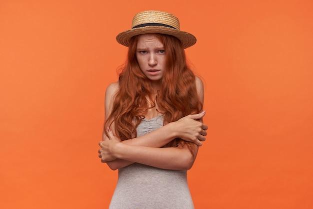 손으로 자신을 포옹, 두려운 카메라를 찾고 오렌지 배경 위에 고립 된 그녀의 얼굴을 찌푸리고 물결 모양의 붉은 lond 머리를 가진 매력적인 젊은 여자의 스튜디오 사진