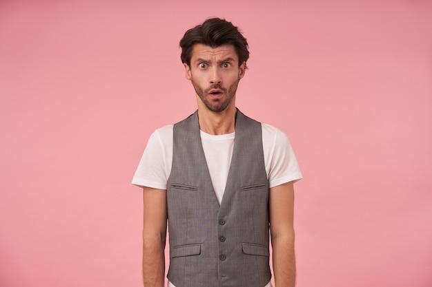 회색 양복 조끼와 흰색 티셔츠에 트렌디 한 머리를 가진 수염 난 어두운 남성의 스튜디오 사진, 손으로 분홍색 배경 위에 포즈, 혼란스러운 얼굴로 카메라를보고, 열린 입으로 인상을 찌푸리고