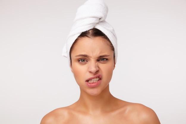 샤워 후 흰색 배경 위에 포즈를 취하는 동안 그녀의 입을 왜곡하고 얼굴을 찡그린 얼굴을하지 않고 아름 다운 젊은 갈색 머리 여성의 스튜디오 사진