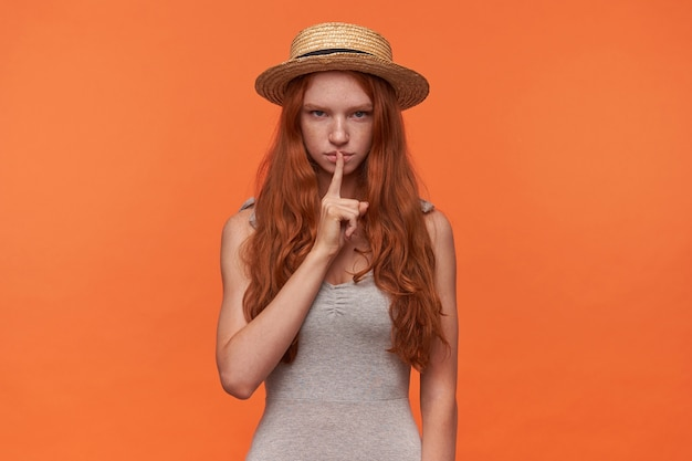 オレンジ色の背景の上に分離された、真面目な顔でカメラを見て、沈黙を求めて、静かなジェスチャーで人差し指を上げる美しい若いフォクシーロンド髪の女性のスタジオ写真