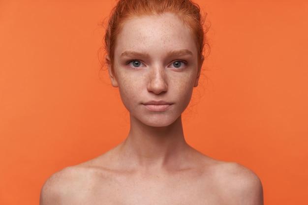 落ち着いた顔でカメラを見て、服なしでオレンジ色の背景の上に立っているカジュアルな髪型の美しい若いreadhead女性のスタジオ写真