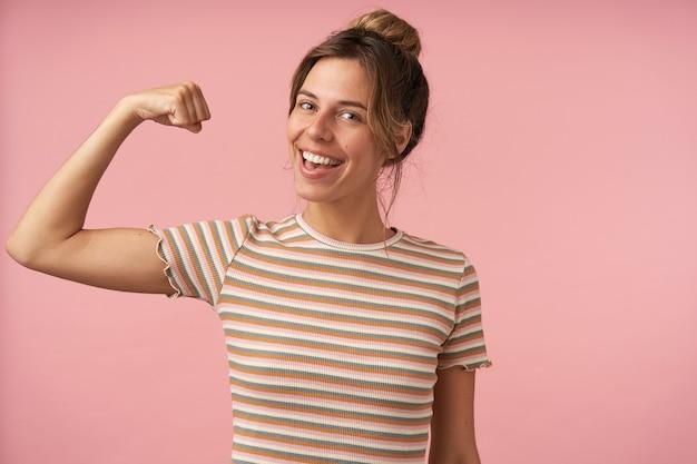 Студийное фото очаровательной молодой брюнетки, одетой в бежевую полосатую футболку, поднимающую руку, демонстрируя свою силу и радостно улыбаясь в камеру, изолированное на розовом фоне