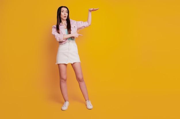 쾌활한 여성의 스튜디오 사진은 노란색 배경 위에 격리된 대형 홀드를 보여줍니다.