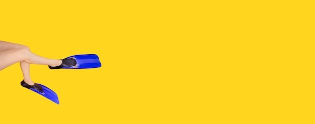 Студийное фото женских ножек в ластах на желтом фоне, концепция летних каникул на море