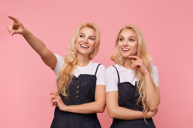 ピンクの背景の上に立って、広い笑顔で不思議に脇を見てエレガントな服を着た嬉しい魅力的な長い髪のブロンドの女性のスタジオ写真