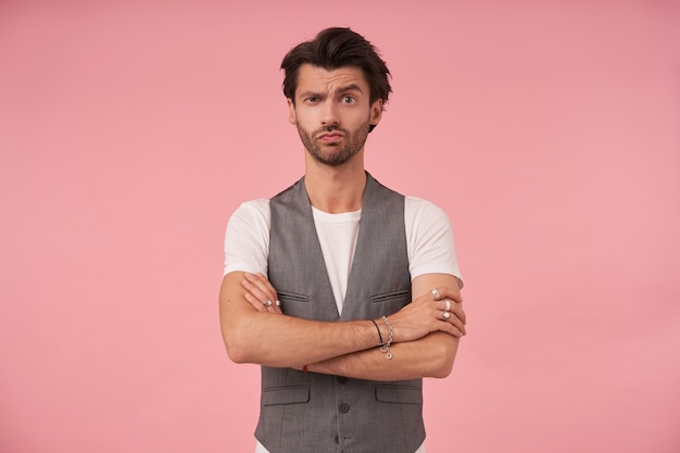 회색 양복 조끼와 흰색 티셔츠에 분홍색 배경 위에 서있는 잘 생긴 검은 머리 남자의 스튜디오 사진, 제기 눈썹으로 카메라를보고, 가슴에 팔을 교차하고 입술을 꽉 쥐고
