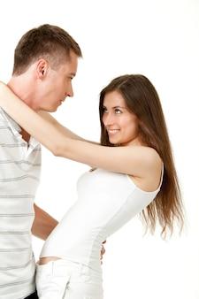 幸せなカップルの男と女が白い背景で隔離のカメラを抱き締めて見ているスタジオ写真