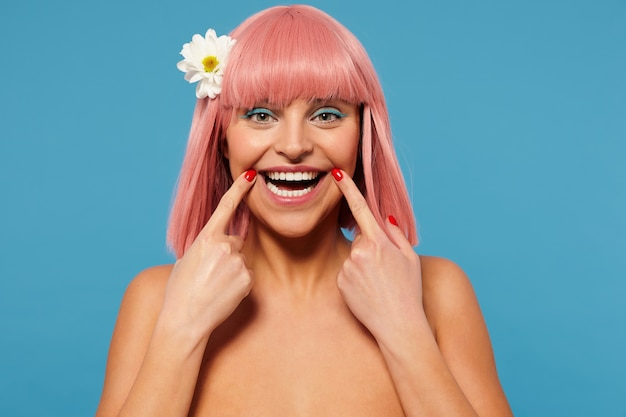 파란색 배경 위에 절연 카메라에 행복하게 웃고있는 동안 짧은 분홍색 머리가 입 모서리에 집게 손가락을 유지하는 즐거운 젊은 녹색 눈을 가진 여자의 스튜디오 사진