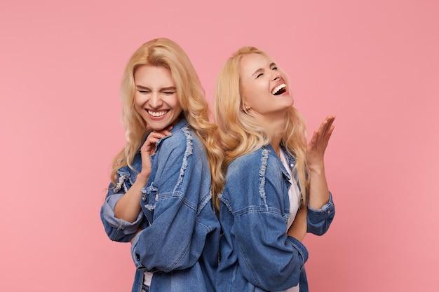 ピンクの背景の上に立っている間、元気で、目を閉じて幸せに笑っている楽しい若い長い髪のブロンドの姉妹のスタジオ写真