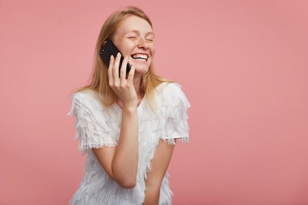 분홍색 배경 위에 포즈를 취하는 동안 축제 티셔츠를 입고 전화로 즐거운 이야기를하면서 닫힌 눈으로 널리 웃고 즐거운 젊은 예쁜 빨간 머리 아가씨의 스튜디오 사진