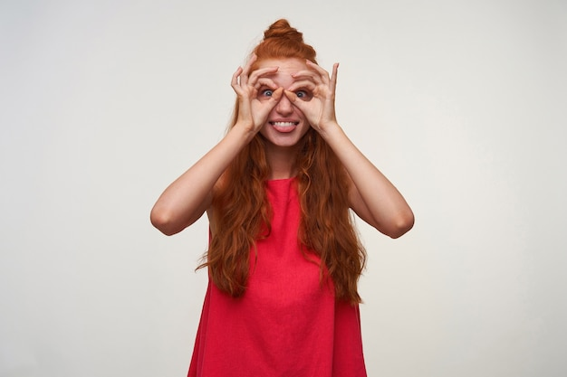 セクシーな髪を結び目で身に着け、白い背景の上にばかげた顔をし、手で眼鏡を作り、舌を見せている楽しい若い女性のスタジオ写真。ポジティブな感情の表情
