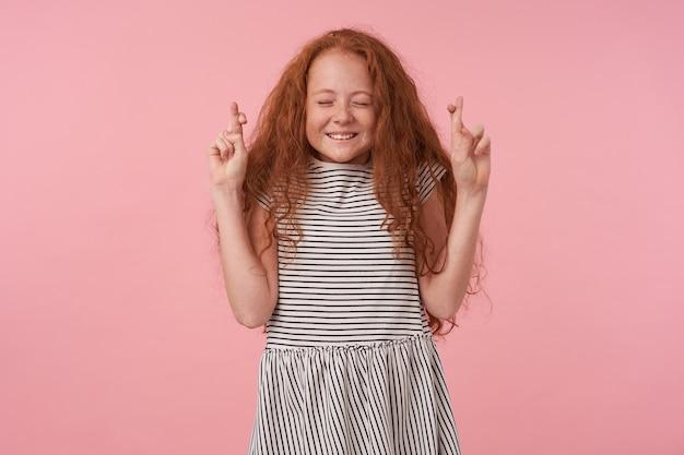 目を閉じてピンクの背景の上に立って、交差した指で手を上げて、心地よい誠実な笑顔で願い事をする長いセクシーな髪のポジティブな巻き毛の女の子のスタジオ写真