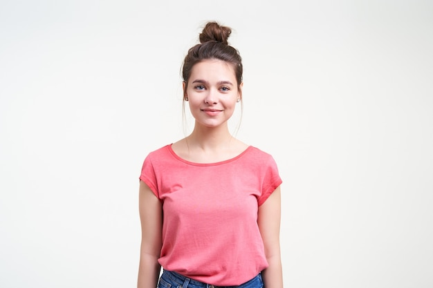 아래로 손으로 흰색 배경 위에 서있는 동안 카메라에 부드럽게 미소 자연 화장과 긍정적 인 젊은 사랑스러운 갈색 머리 여성의 스튜디오 사진