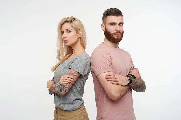 가슴에 손을 교차하고 흰색 배경 위에 서있는 접힌 입술로 카메라를 심각하게보고 젊은 사람들의 예쁜 쌍의 스튜디오 사진