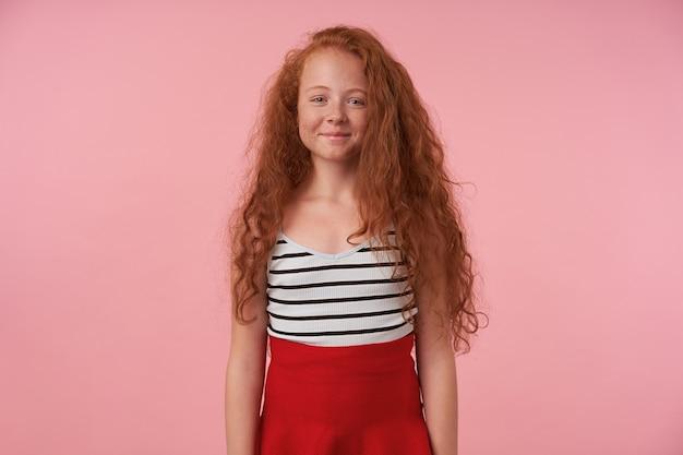 ピンクの背景の上に手を下ろしてポーズをとって、魅力的な笑顔でカメラを見て、赤いスカートとストライプのトップを着て、長い巻き毛のかわいい赤毛の女の子のスタジオ写真
