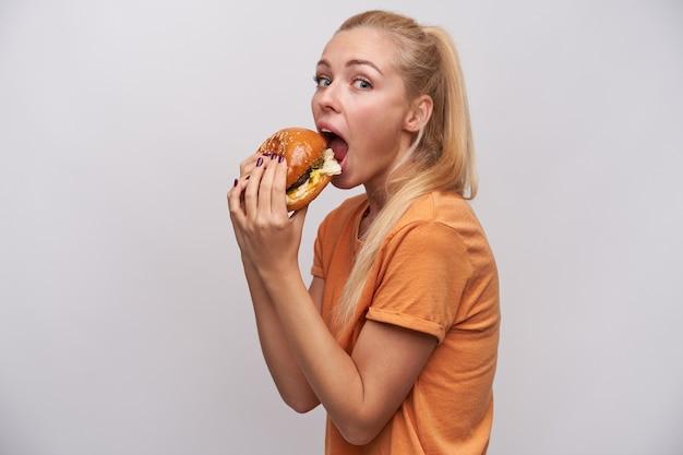彼女の手でおいしいハンバーガーを持って、白い背景に立ってそれを食べに行くカジュアルな服装でかなり若い長い髪のブロンドの女性のスタジオ写真
