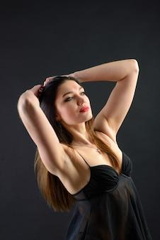 Студийное фото соблазнительной женщины в черном белье на фоне студии