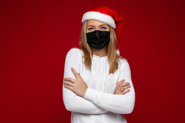 Фото студии серьезной белокурой дамы, носящей шляпу санты и респираторную маску, представляя в красной предпосылке. копировать пространство