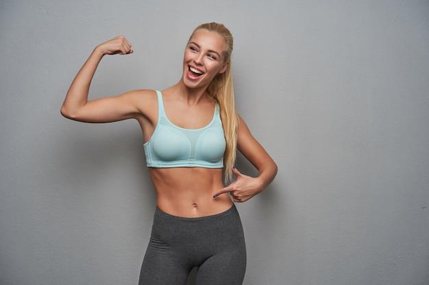 Студийное фото стройной спортивной радостной женщины с длинными светлыми волосами, поднимающей руку и демонстрирующей свои бицепсы, в спортивной одежде, стоя на светло-сером фоне, пребывающей в приподнятом настроении