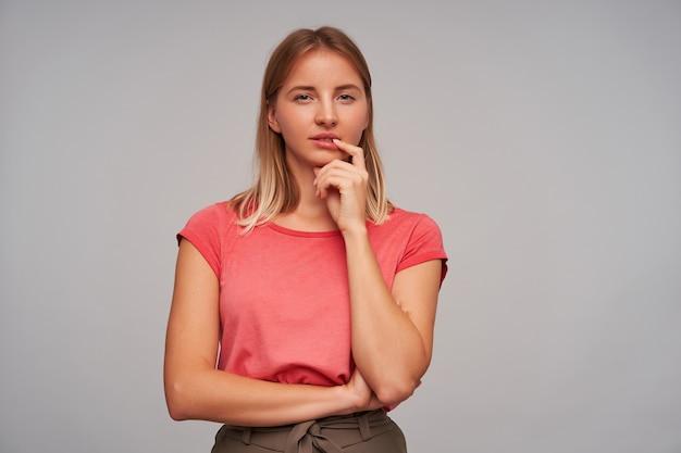 Студийное фото задумчивой симпатичной молодой леди с короткими светлыми волосами и повседневной прической, позирующей на белом фоне, держащей рукой подбородок и смотрящей в камеру со сложенными губами