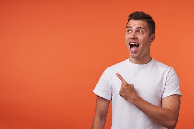 オレンジ色の背景の上に分離された、脇を指して口を大きく開いたまま人差し指を上げたまま短いヘアカットで若い驚いたブルネットの男のスタジオ写真