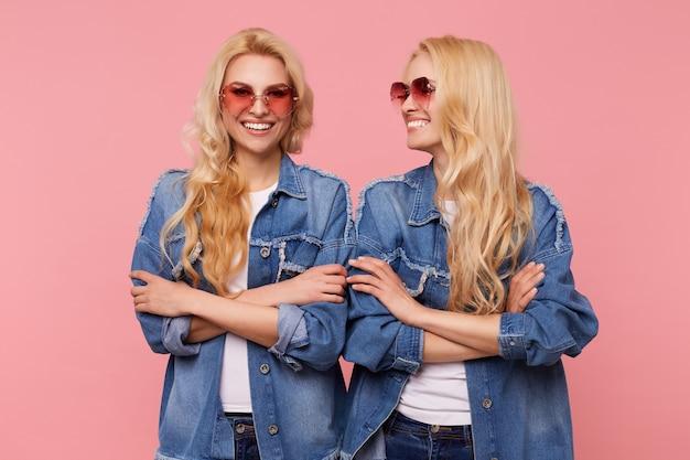 胸に手を交差させ、ピンクの背景の上に立っている間喜んで笑っている長いウェーブのかかった髪を持つ若い魅力的な陽気な白い頭の女性のスタジオ写真