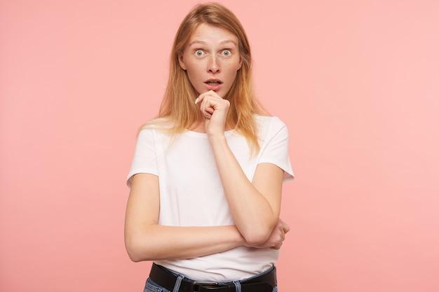 분홍색 배경 위에 절연 넓은 눈을 가진 카메라를 놀랍게 보면서 제기 손으로 그녀의 턱을 들고 젊은 멍청한 빨간 머리 여성의 스튜디오 사진이 열렸습니다.