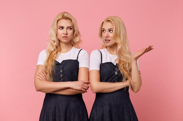 ピンクの背景に立っているジーンズのドレスと白いtシャツに身を包んだ若い当惑したかなり長い髪の白い頭の女性のスタジオ写真