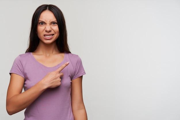 人差し指で脇に表示し、白い背景の上に分離されたカメラを見ながら不満を持って彼女の顔を顔をゆがめている若い茶色の目の暗い髪の女性のスタジオ写真
