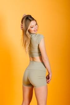 젊은 백인 여성 운동선수의 스튜디오 사진입니다. 섹시한 운동복을 입고 슬림 금발의 여자