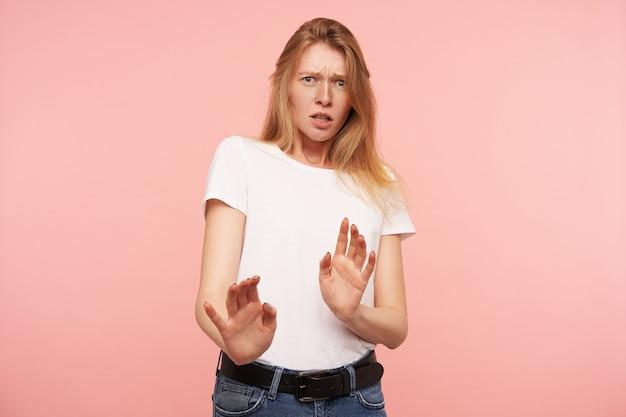 ピンクの背景の上に分離された、カメラを怖がって見ながら保護ジェスチャーで手のひらを上げるカジュアルな髪型を持つ若い混乱した赤毛の女性のスタジオ写真