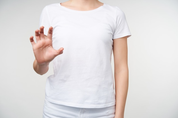 白い背景の上に立って、手話を使用して単語の写真家を示す間、彼女の手を上げたままカジュアルな服を着た若い女性のスタジオ写真