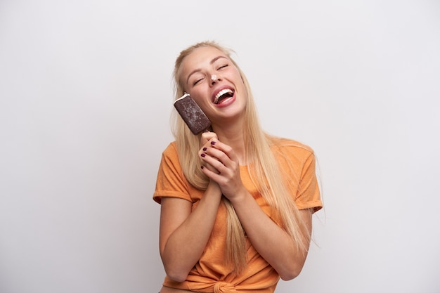 目を閉じて幸せそうに笑って、白い背景の上に分離された彼女の手でアイスクリームをだましてオレンジ色のtシャツで若い格好良い長い髪のブロンドの女性のスタジオ写真