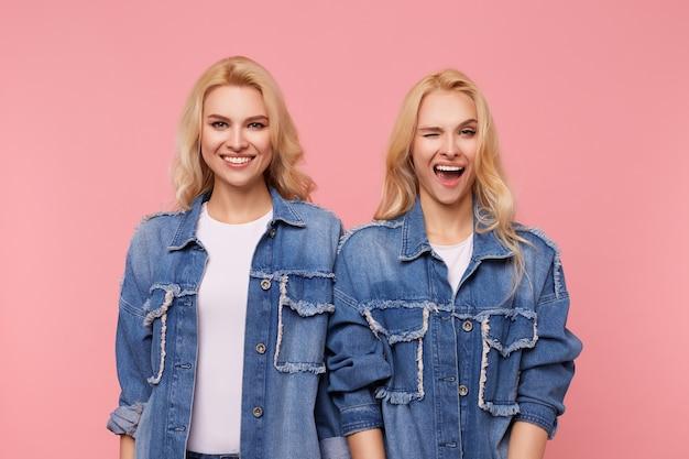 물결 모양의 헤어 스타일이 좋은 분위기에 있고 캐주얼 옷에 분홍색 배경 위에 서있는 동안 행복하게 웃고있는 젊은 사랑스러운 국방과 여성의 스튜디오 사진