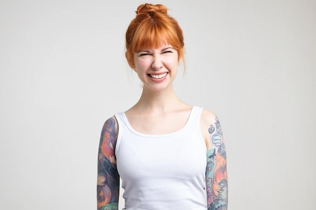 즐겁게 웃고있는 동안 그녀의 눈을 가늘게 뜨고있는 문신을 가진 젊은 사랑스러운 빨간 머리 여자의 스튜디오 사진, 흰색 배경 위에 포즈를 취하는 동안 높은 정신에