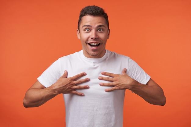 オレンジ色の背景の上に立って、広い笑顔でカメラを興奮して見て、胸に手を上げたまま、短いヘアカットを持つ若いかなりブルネットの男性のスタジオ写真