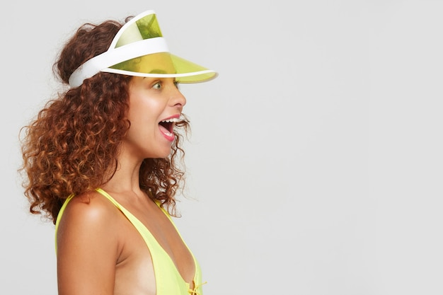 젊은 예쁜 빨간 머리 곱슬 여성의 스튜디오 사진은 수영 착용에 흰색 배경 위에 절연, 감정적으로 앞서 보면서 놀란 눈썹을 제기